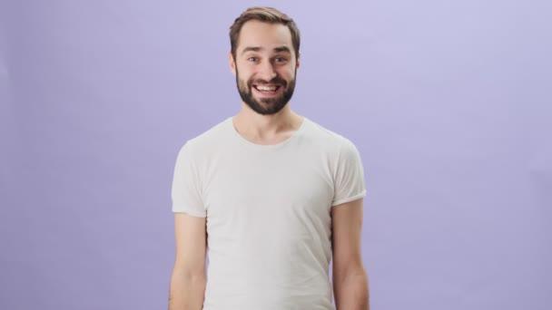 Ein fröhlicher junger Mann im weißen T-Shirt zeigt mit beiden Händen Daumen nach oben, während er isoliert vor grauem Hintergrund steht.