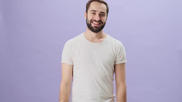 Egy boldog, boldog fiatalember fehér pólóban nevet, miközben elszigetelve áll szürke háttér felett.