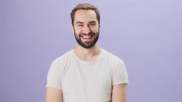 Šťastný veselý mladý muž v bílém tričku se směje stojí izolovaně přes šedé pozadí