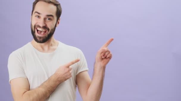 Šťastný usměvavý mladý muž v bílém tričku ukazuje na volné místo, obě ruce stojí izolovaně nad šedým pozadím