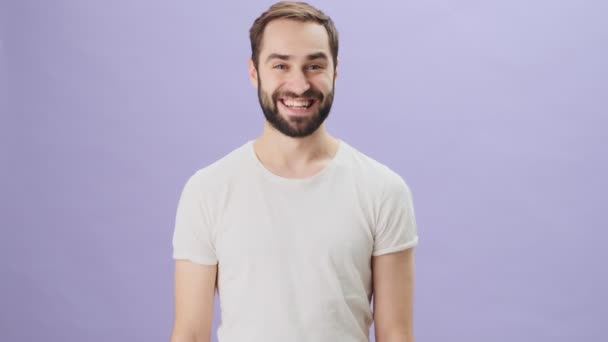 A happy joyful young man wearing a white t-shirt is raising both his hands standing isolated over gray background