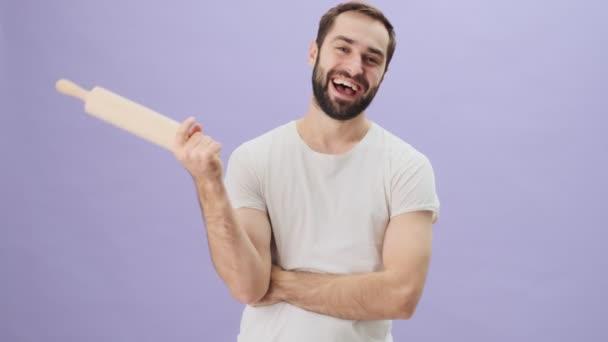 Šťastný radostný mladý muž v bílém tričku drží váleček stojící izolovaně nad šedým pozadím