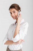 Kép elégedett gyönyörű nő mosolyog és beszél a mobiltelefon elszigetelt fehér háttér