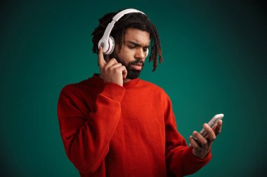 Portrait of serious african american man using cellphone and wireless headphones isolated over green background