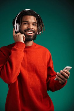 Portrait of laughing african american man using cellphone and wireless headphones isolated over green background