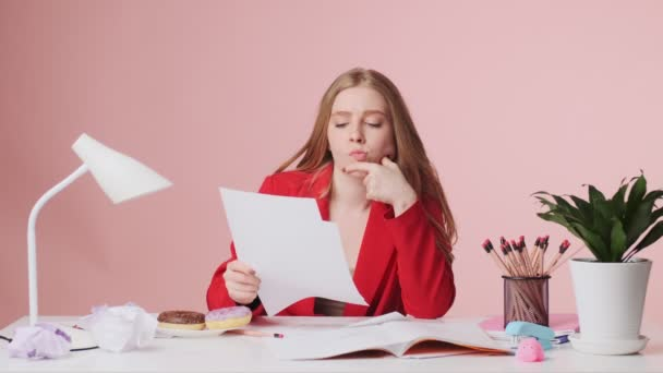 A focused young woman is reading paper documents something while sitting at the table isolated over pink background