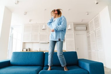 Image of cute smiling woman dancing on couch while using wireless headphones at home