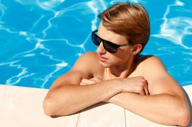 Close up portrait of attractive young man  in sunglasses resting
