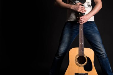Guitarist holding two hands with an acoustic guitar on a black isolated background