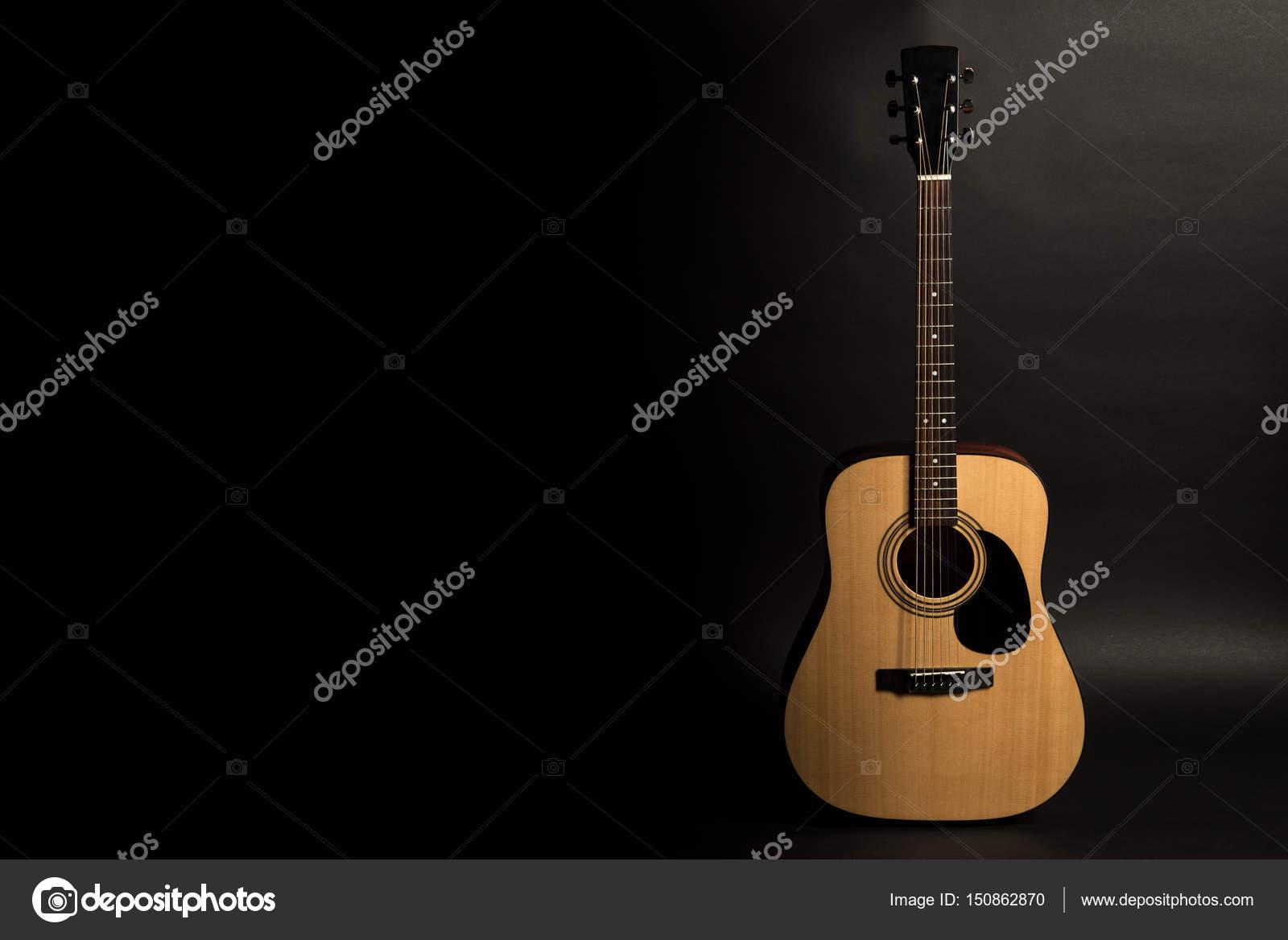 Violão em um fundo preto no lado direito do quadro instrumento de