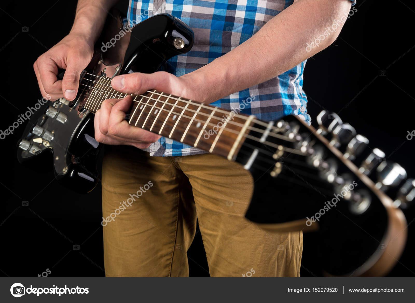 Música e arte o guitarrista detém uma guitarra nas mãos sobre um