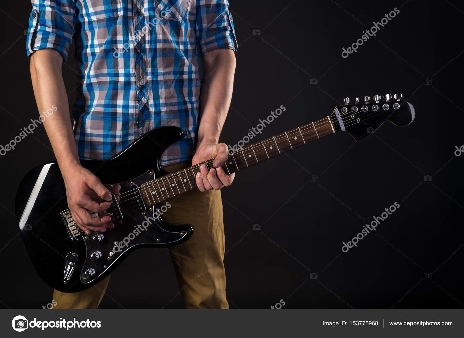 Música e arte o guitarrista detém uma guitarra elétrica na mão