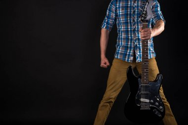 Music and art. The guitarist holds an electric guitar in his left hand, on a black isolated background. Playing guitar. Horizontal frame
