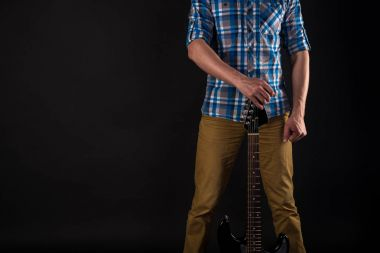 Music and art. The guitarist holds an electric guitar in his right hand, on a black isolated background. Playing guitar. Horizontal frame