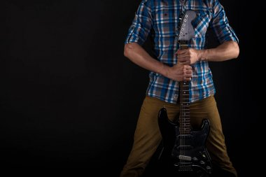 Music and art. The guitarist holds the electric guitar with his hands, on a black isolated background. Playing guitar. Horizontal frame