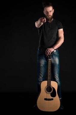 A charismatic and stylish man with a beard stands full-length with an acoustic guitar on a black isolated background. Vertical frame