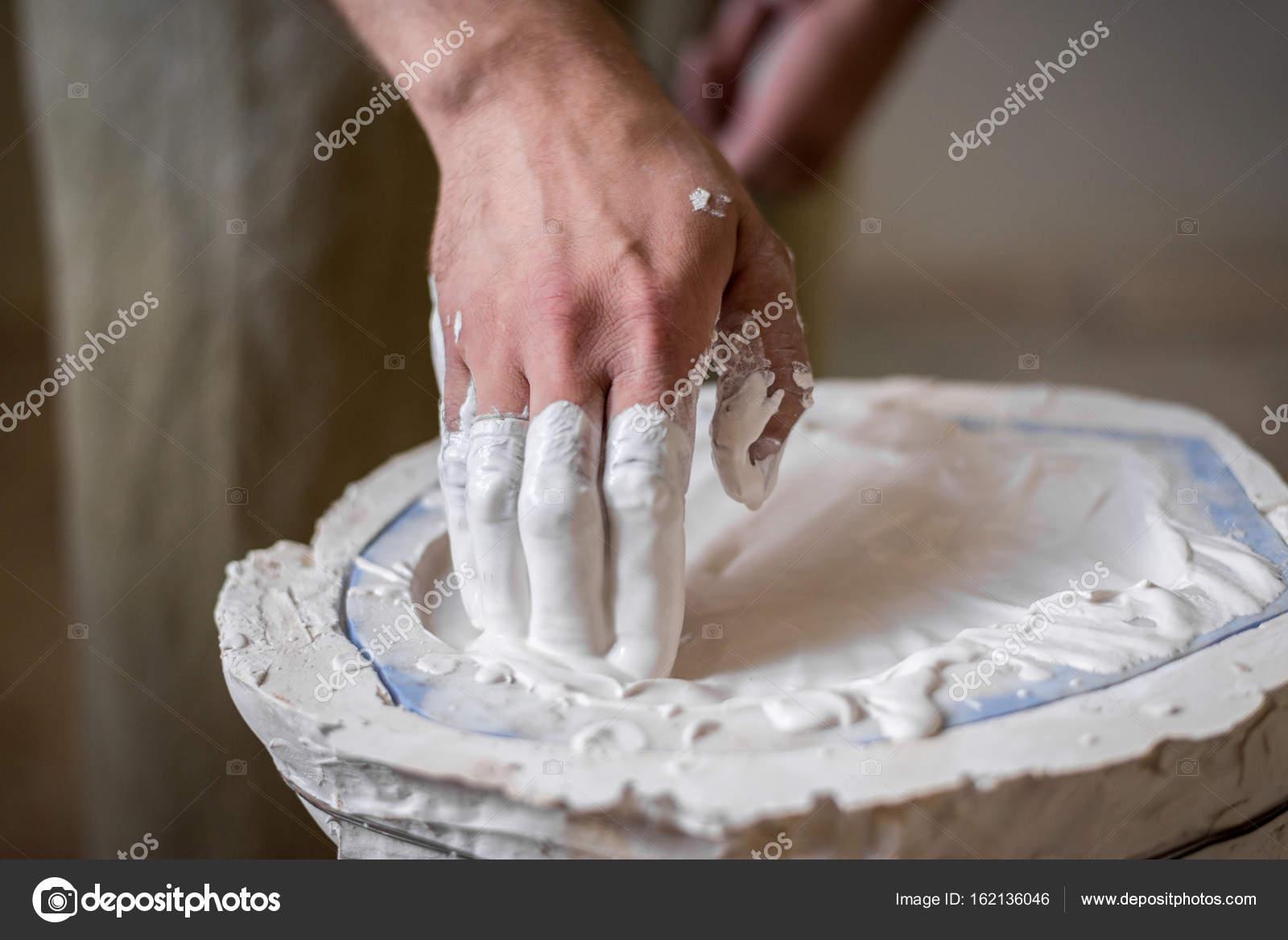 Las manos del escultor llenan el blanco líquido en el molde. Marco ...