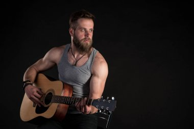 A charismatic man with a beard, playing an acoustic guitar, on a black isolated background. Horizontal frame