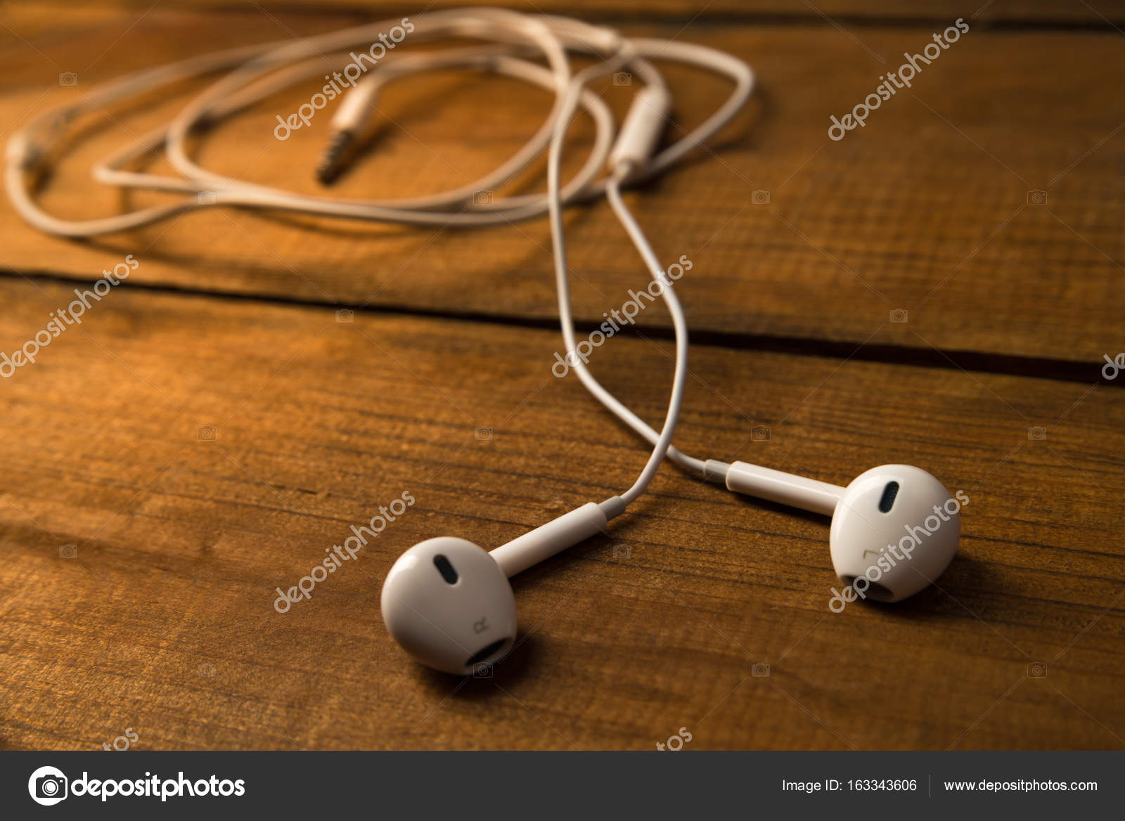 White Little Headphones On A Wooden Isolated Background Horizontal