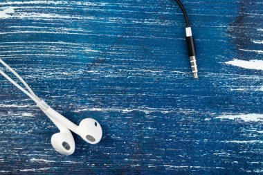 Small white headphones and a black plug lie on a blue denim background. Horizontal frame
