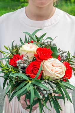 wedding white-red bouquet in the hands of the bride