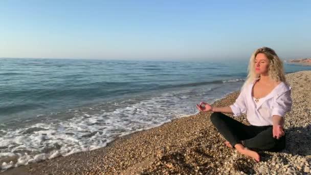 Krásná blondýnka sedí a medituje na pláži v blízkosti vln modrého moře.Krym, Sevastopol.
