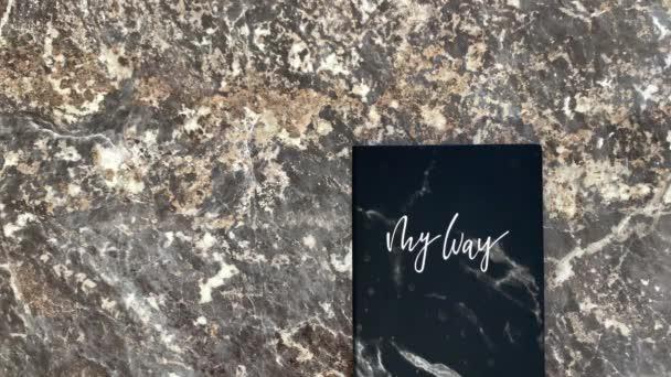 Hihetetlen kozmikus gyönyörű fekete napló egy fekete márvány háttér, kinyílik, és lehet jegyzetelni. Lapozgatás. Felülnézet.