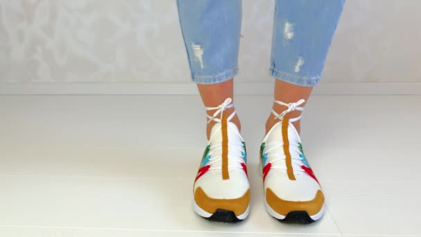 Die schlanken Beine der Frauen in Jeans und Turnschuhen. Beim Umzug wechseln die Turnschuhe gegen neue. viele Turnschuhe in verschiedenen Farben.