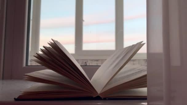 Egy nyitott könyv fekszik az ablakpárkányon, kívül az ablakon naplemente, mellette olvasószemüveg. Lassú mozgás..