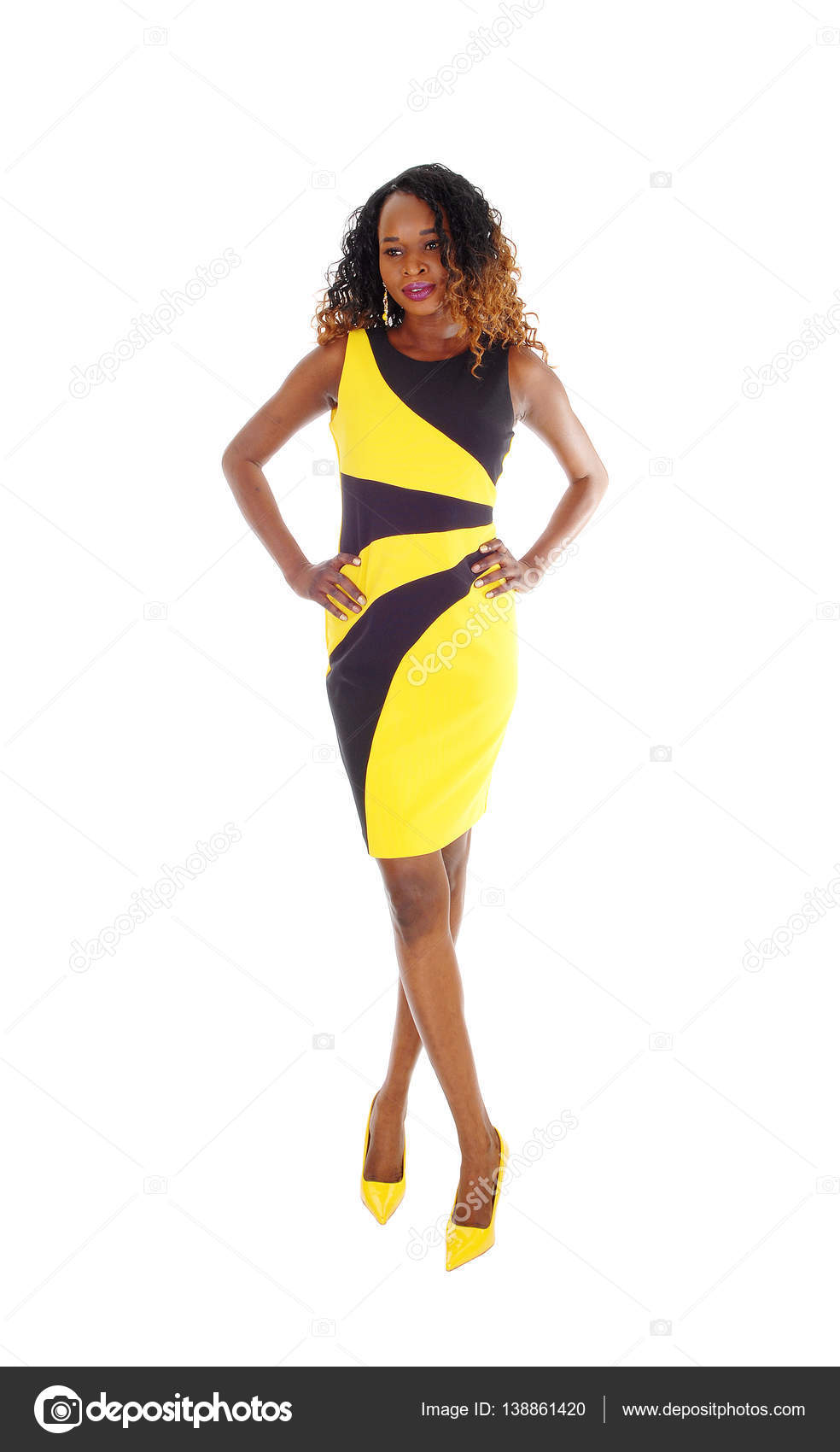 cbb74dc02a1 A beautiful African American slim woman standing in a black and yello —  Photo by ...