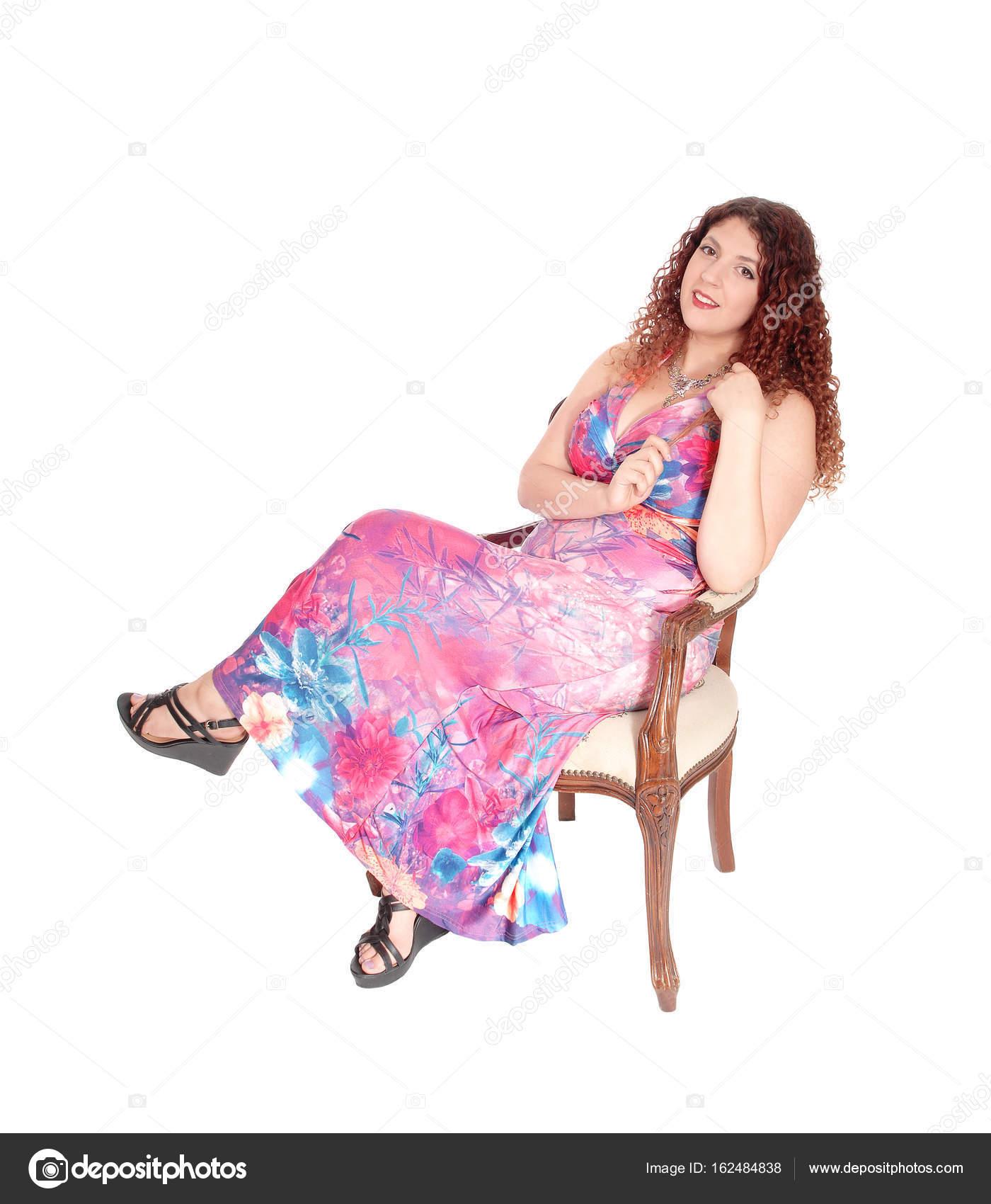 Mujer hermosa en un vestido largo sentado en sillón — Foto de stock ...
