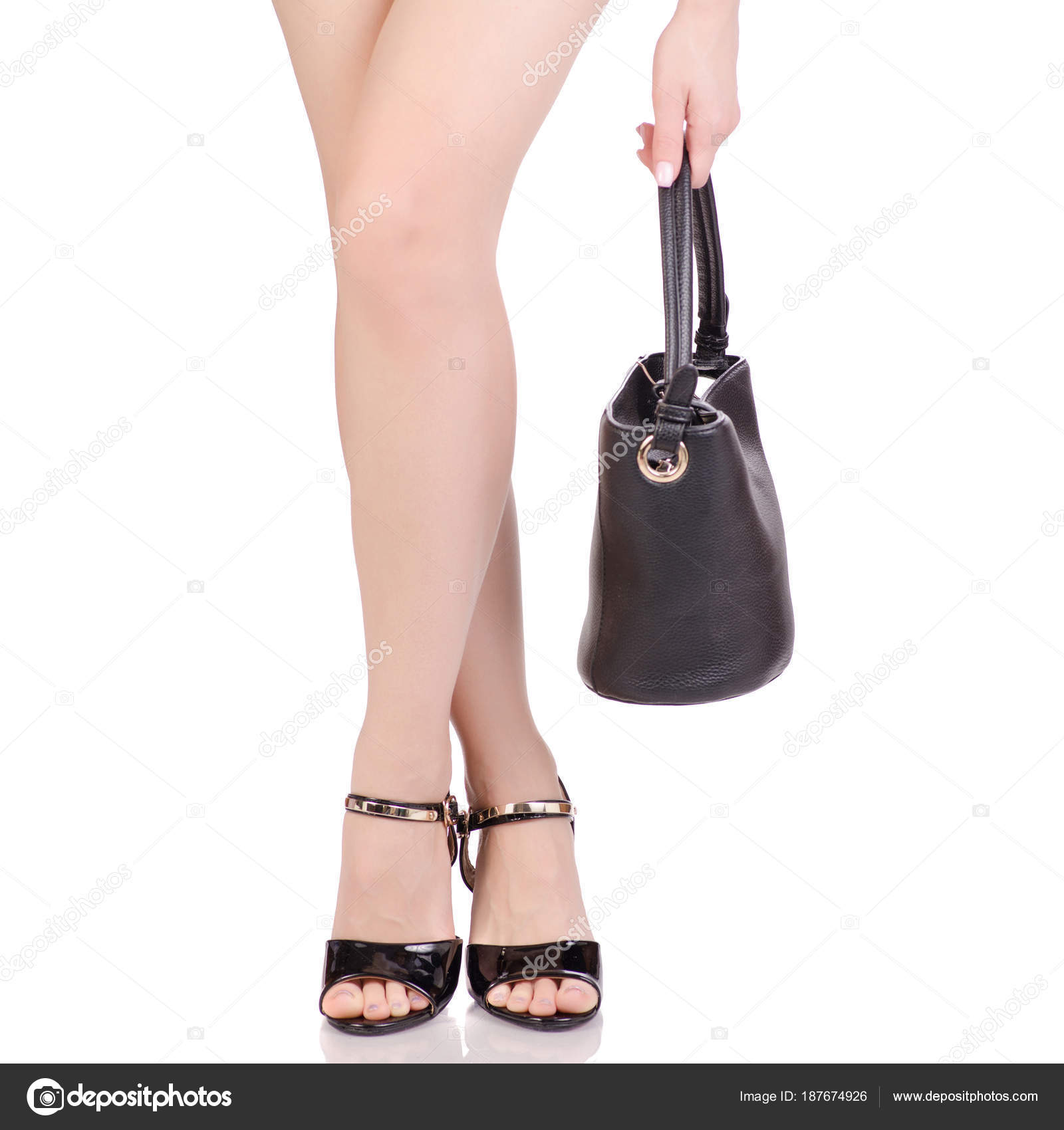 c5deadad1 Female legs in black lacquered shoes sandals and black leather handbag  beauty fashion buy shop on white background isolation — Photo by ...