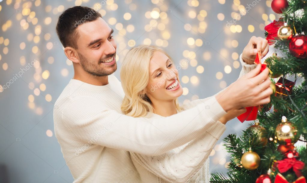 family x mas winter holidays and people concept happy couple decorating christmas tree over lights background photo by syda_productions - People Decorating A Christmas Tree