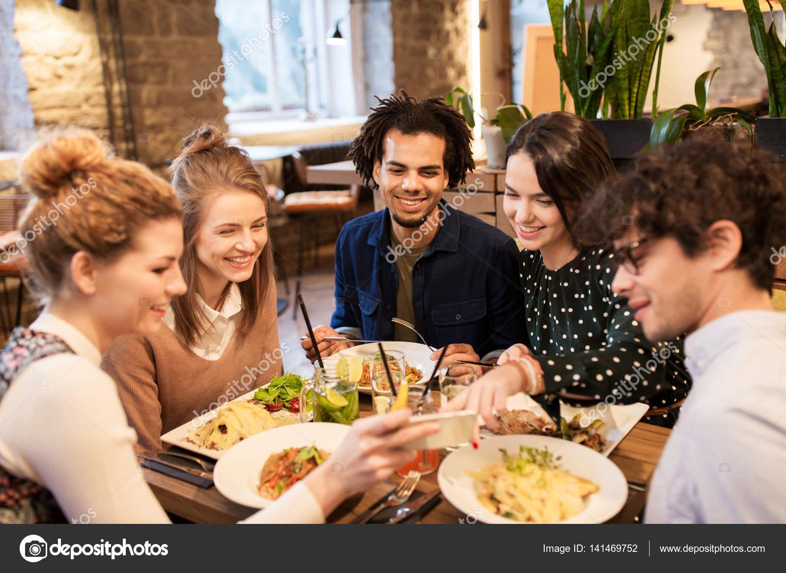 Freunde mit Smartphones essen im Restaurant