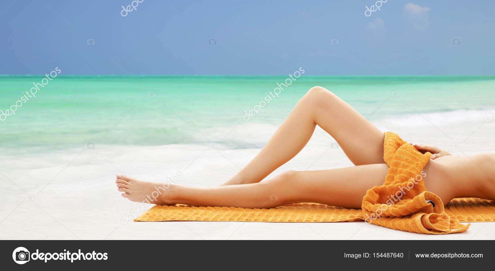 c8446fce259e Piernas de mujer desnuda acostada en toalla en la playa — Foto de ...