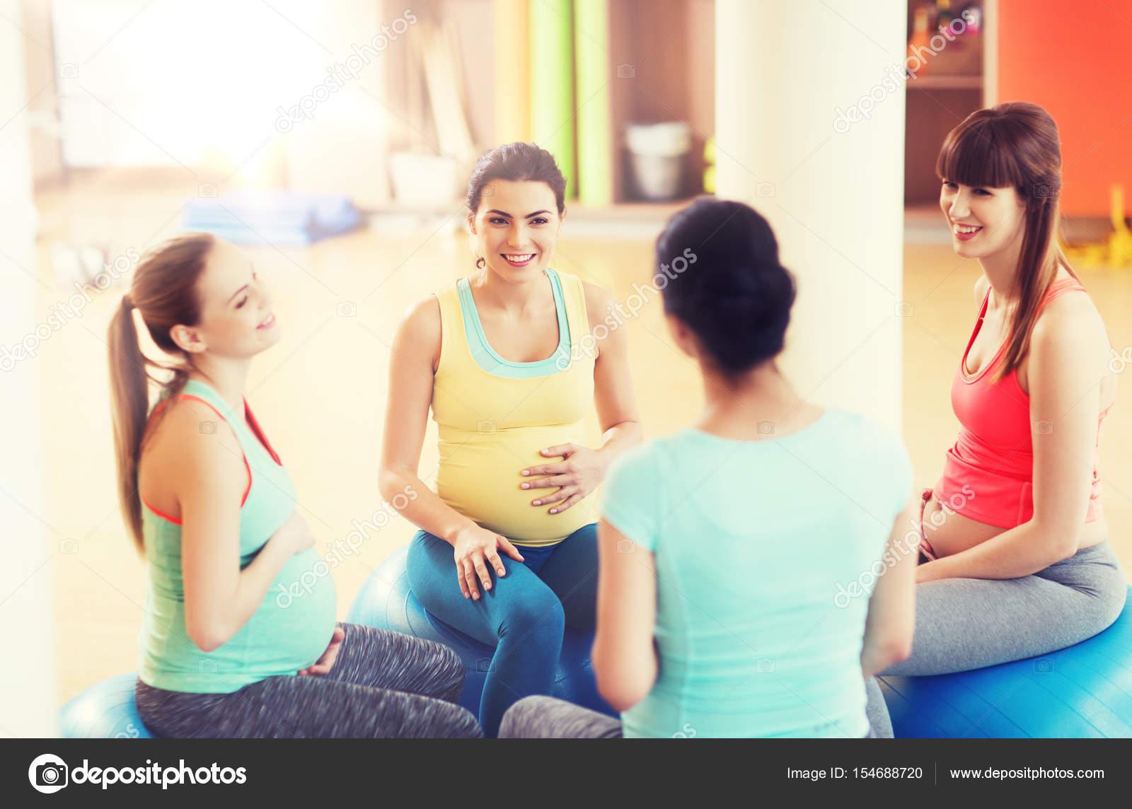 glückliche schwangere Frauen sitzen auf Bällen in Turnhalle ...