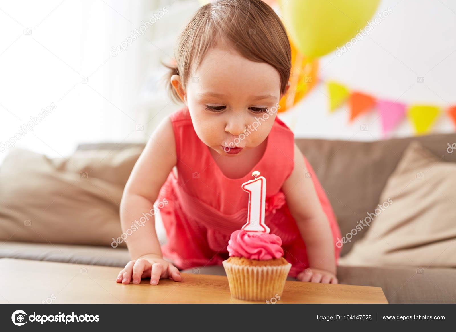 Madchen Blast Zur Kerze Auf Cupcake Am Geburtstag Stockfoto