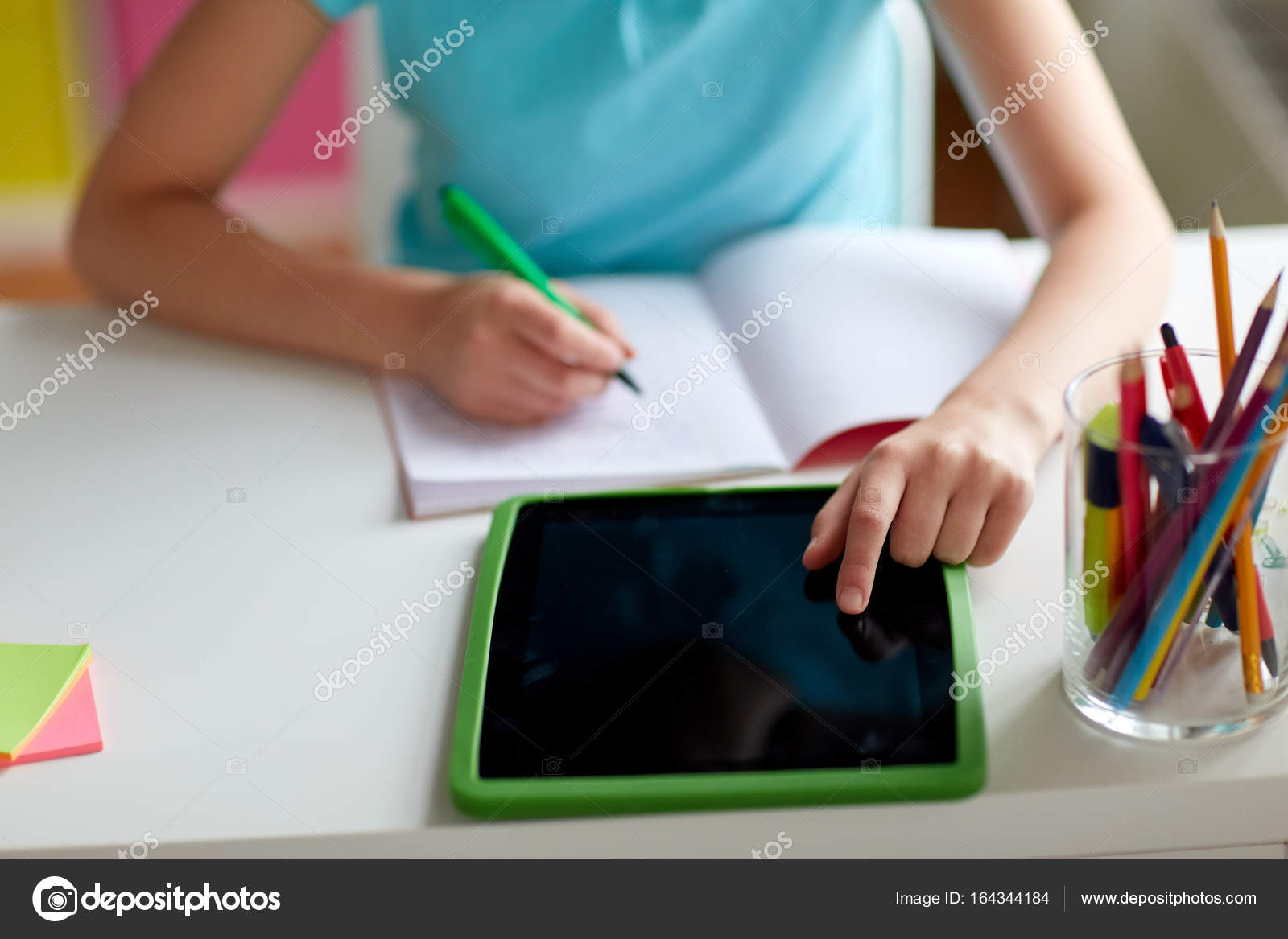 girl with tablet pc writing to notebook at home — Stock