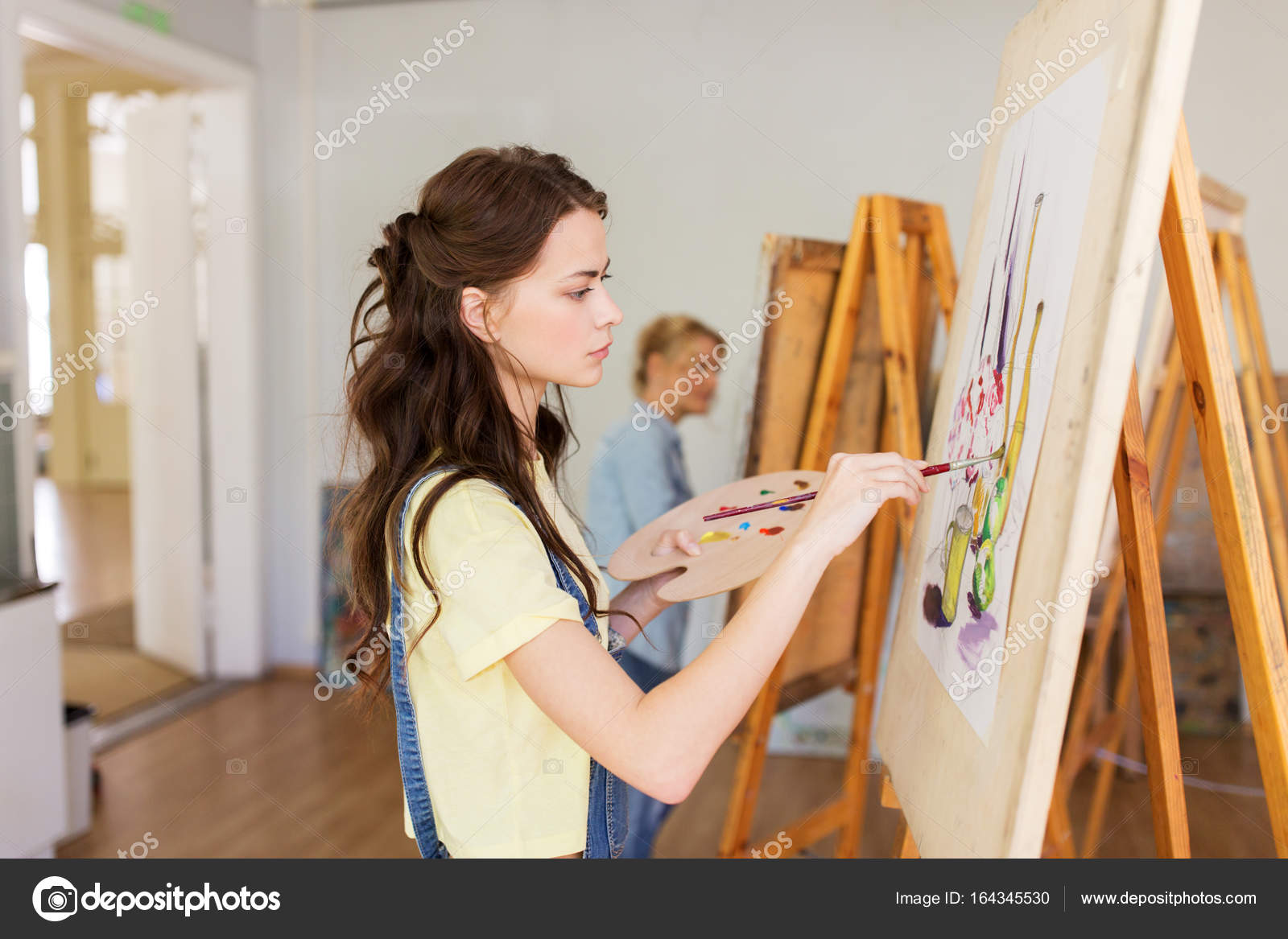 Student Girl With Easel Painting At Art School Stock Photo