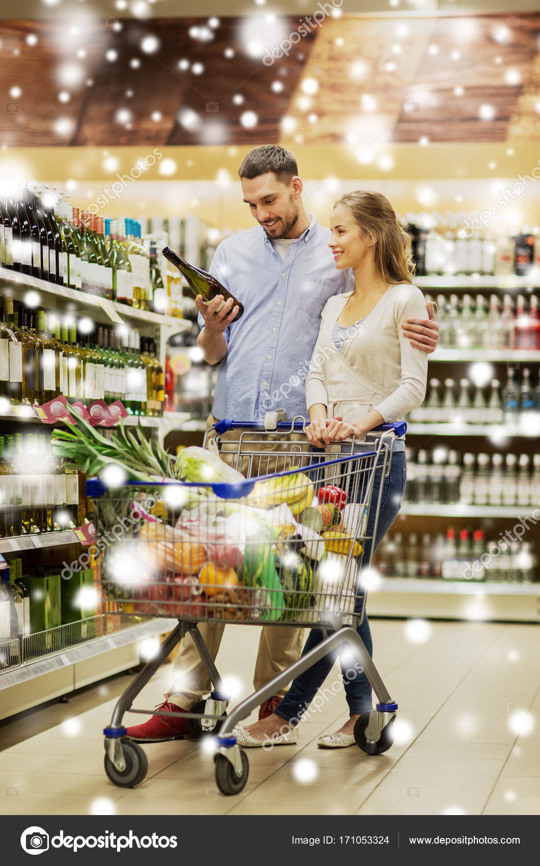 Couple With Wine And Shopping Cart At Liquor Store Stock