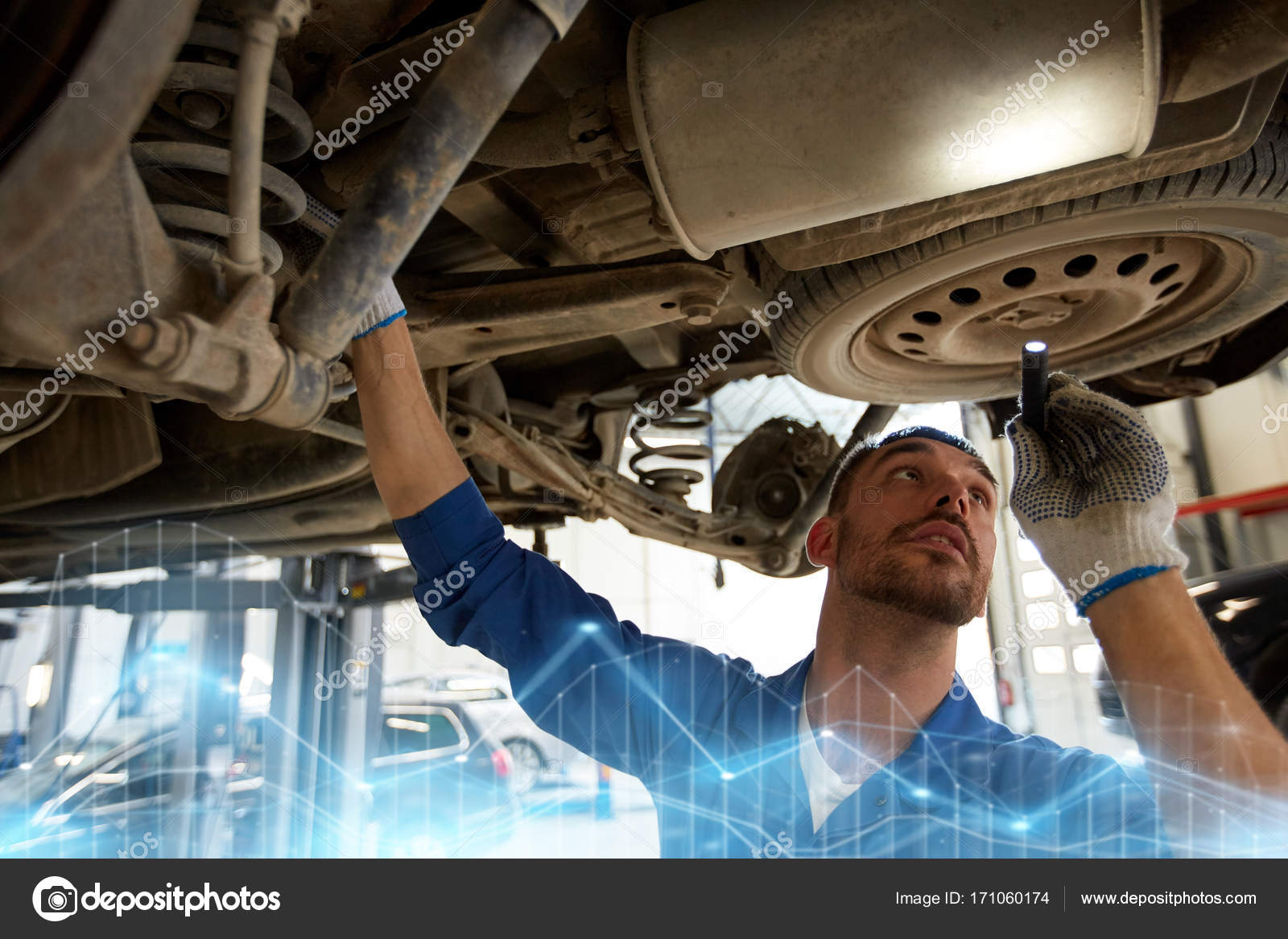 mechanic man with flashlight repairing car at shop stock photo