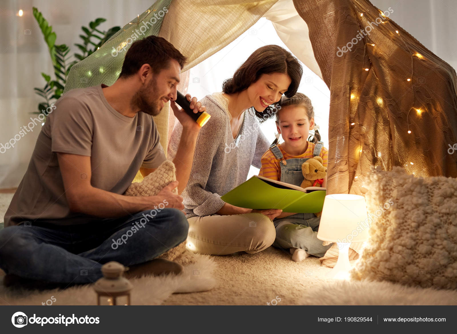Happy family reading book in kids tent at home stock photo family hygge and people concept happy mother father and little daughter reading book with torch light in kids tent at night at home photo by sciox Gallery