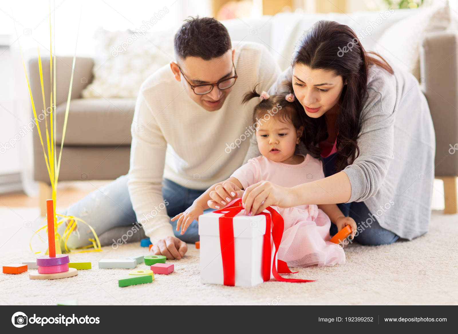 Baby Girl With Birthday Gift And Parents At Home Stock Photo