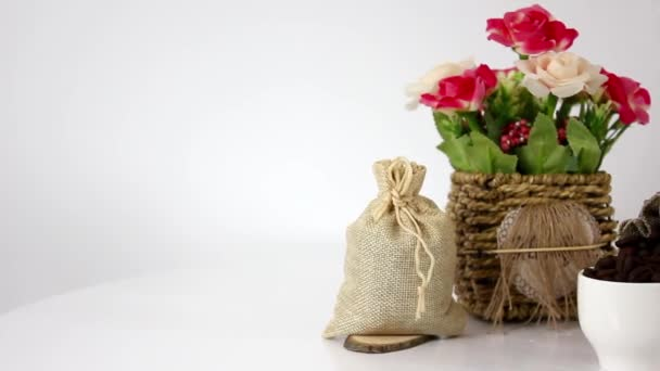flowers with bags and cup with coffee beans on spinning table background
