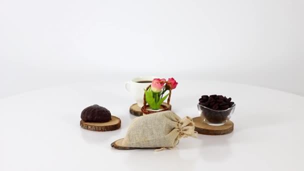 kávécsésze kávébab és virágok a forgó asztal háttér