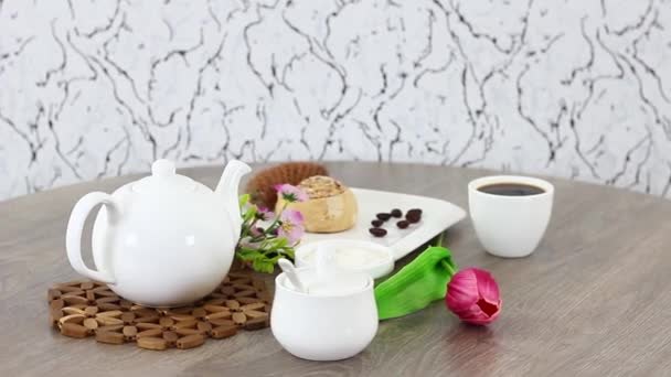 white kettle with coffee cup and buns on spinning wooden table background