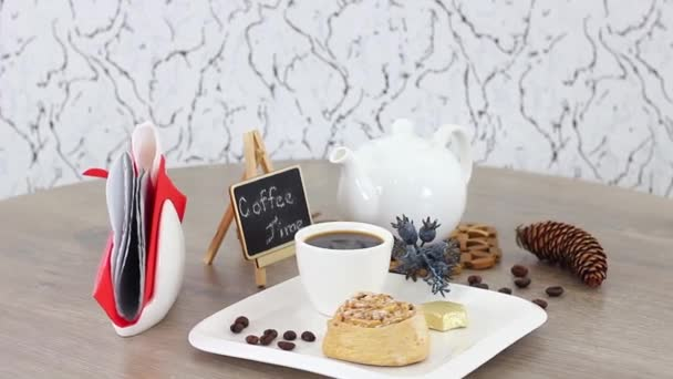 white kettle and coffee cup with bun and coffee beans on spinning wooden table background