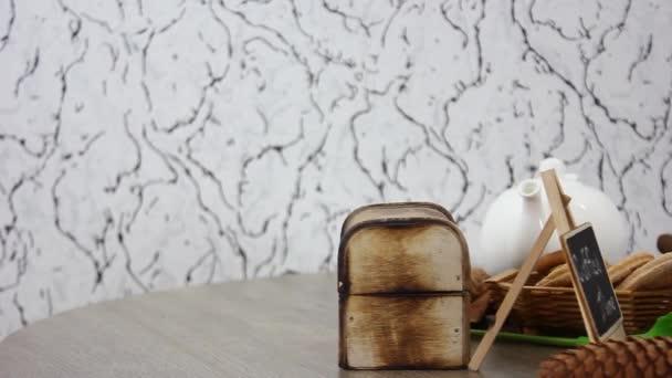 koš se sušenkami a šálkem kávy s tulipánem a dřevěnou krabicí na točícím se dřevěném stole na pozadí