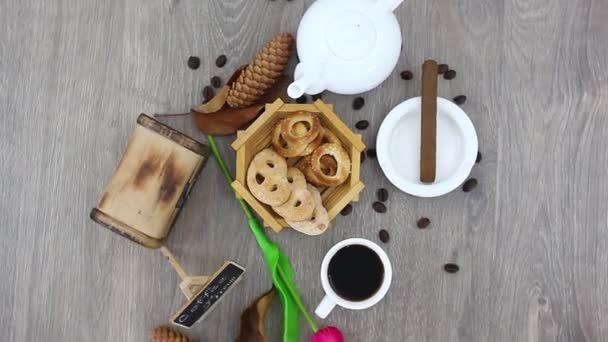 cookies in basket with kettle and coffee cup with wooden box on spinning wooden table background