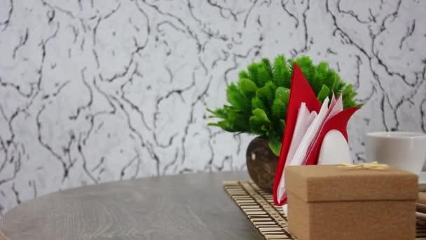 Brötchen und süße Sticks mit Kaffeetasse mit grüner Pflanze im Topf auf drehbarem Holztischhintergrund